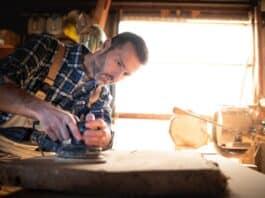 Carpenter at workshop polishes wooden board with a electric orbital sander