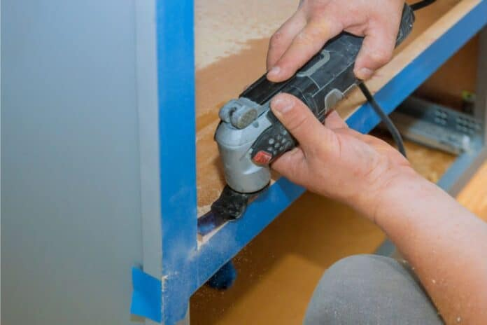 using oscillating multi functional cutting tool for handyman cut hole in kitchen furniture